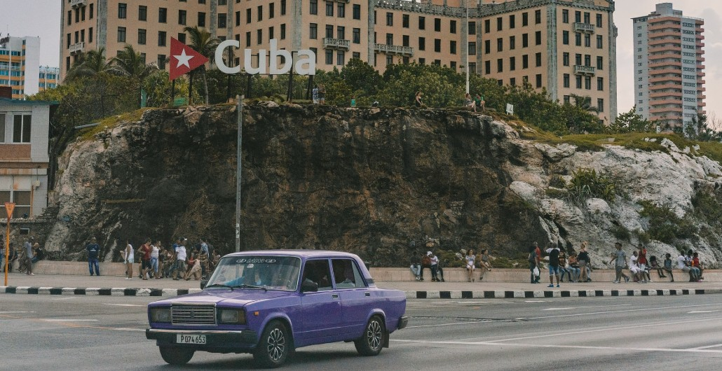 Car in Front of Cuba Sign
